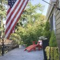 Front porch with red adirondack chair, planters and an American flag. Happy 4th of July!