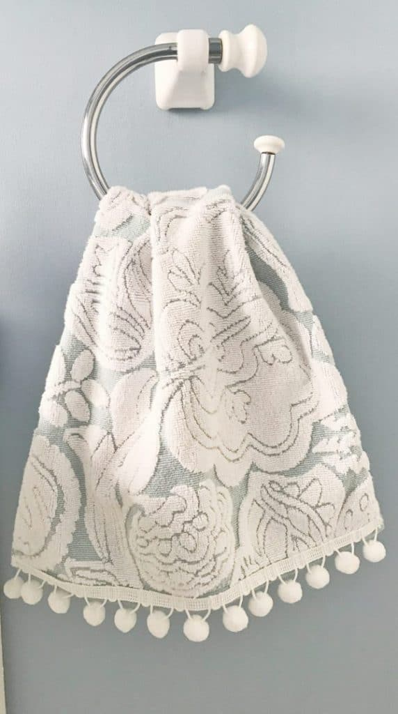 Towel with pom pom trim hanging on towel holder