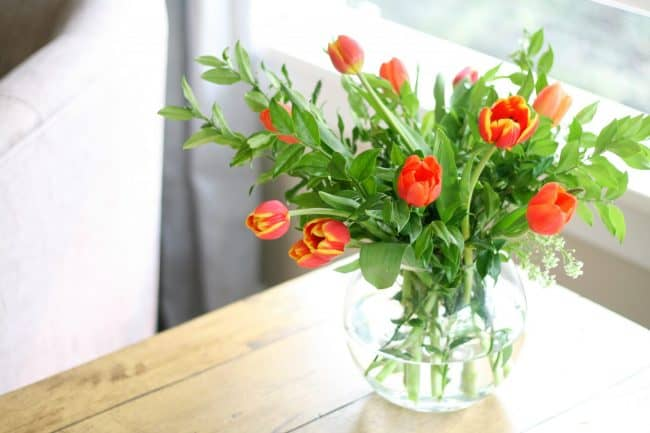 This tutorial will show you how to make a simple fall flower arrangement.  Orange and red tulips with backyard greenery make this simple but pretty and really inexpensive.  Make a grid from tape to help stabilize the flower arrangement.  You will want to make a few to display around your home for fall!