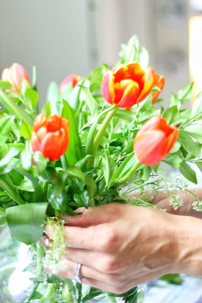 This tutorial will show you how to make a fall flower arrangement. Orange and red tulips with backyard greenery make this simple but pretty and really inexpensive. Make a grid from tape to help stabilize the flower arrangement. You will want to make a few to display around your home for fall!
