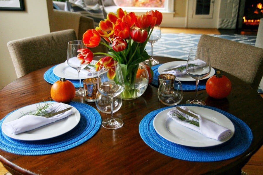 Blue placemats, white dishes and orange tulips for THanksgiving