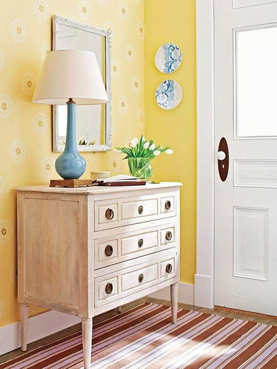 Small foyer area with lamp and chest of drawers