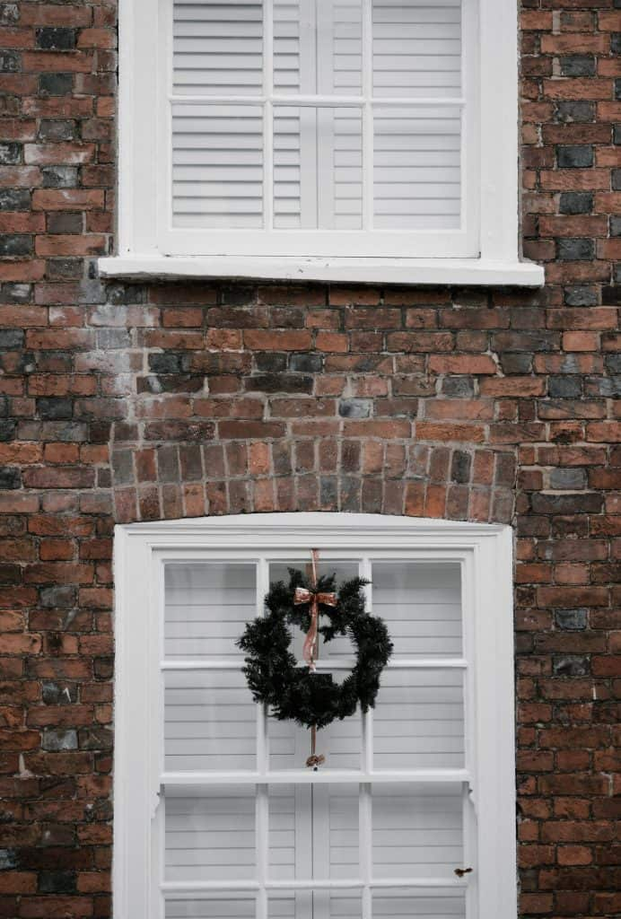 How to Style Your store bought Christmas Wreath - Take a plain, cheap, boring Christmas wreath and turn it into something you are proud to display.  Get all the tips and tricks for how to style your store bought Christmas wreath here!