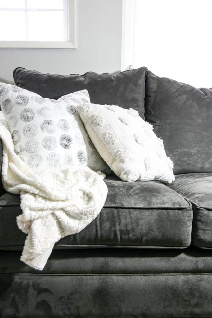 Pillows on a couch with a white throw