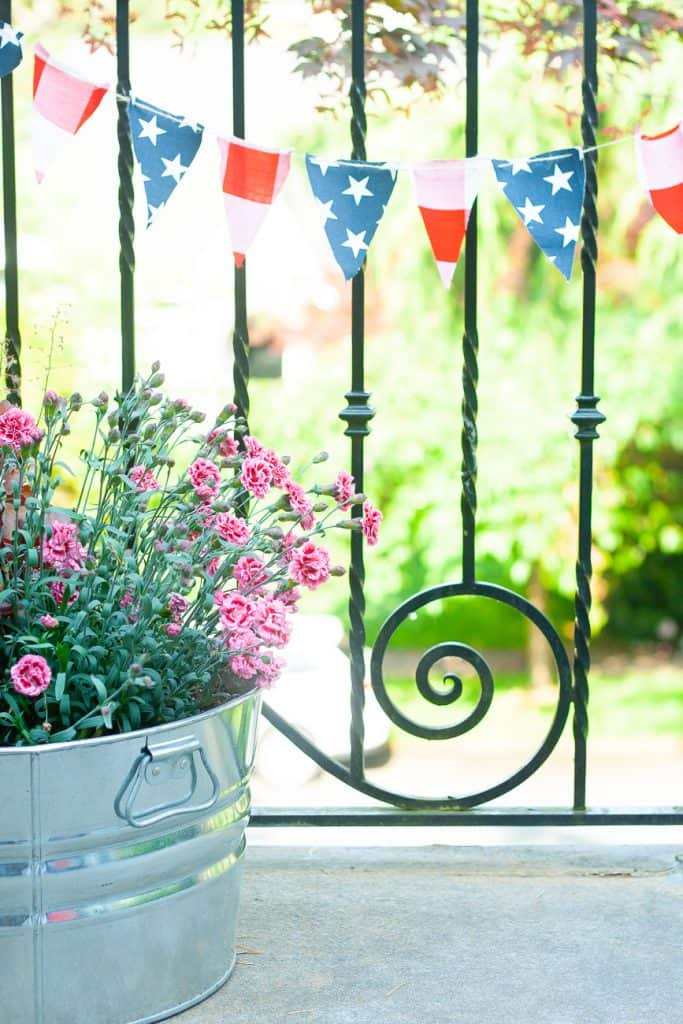 A festive 4th of july banner hanging next to summer flowers
