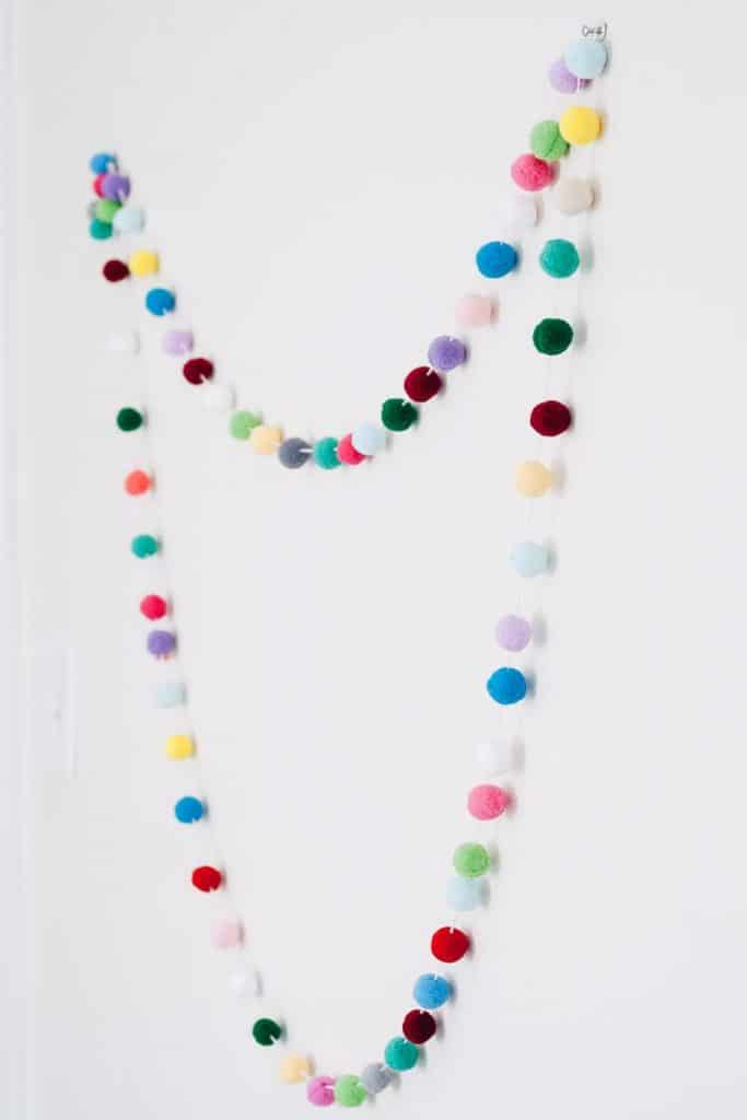 Make this colorful and fun diy pom pom garland.  This gives your room great pops of color and is easy to hang and drape on anything.  This makes a great addition to your kids rooms and nurseries, but also your home office too for a creative spin on decorating.  Just three simple materials and you are on your way.  Also makes awesome, inexpensive party decor!  #diy #crafts #pompom #kidsroom