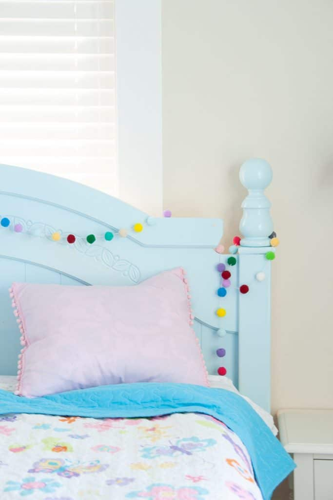 Make this colorful and fun diy pom pom garland. This gives your room great pops of color and is easy to hang and drape on anything. This makes a great addition to your kids rooms and nurseries, but also your home office too for a creative spin on decorating. Just three simple materials and you are on your way. Also makes awesome, inexpensive party decor!#diy #crafts #pompom #kidsroom
