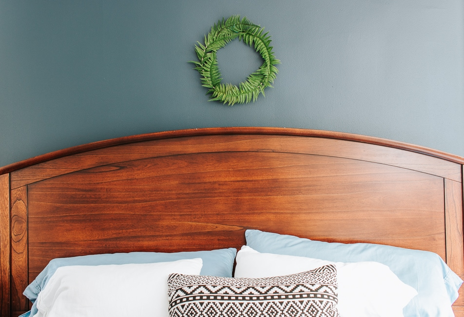 Fern wreath hanging above a bed.