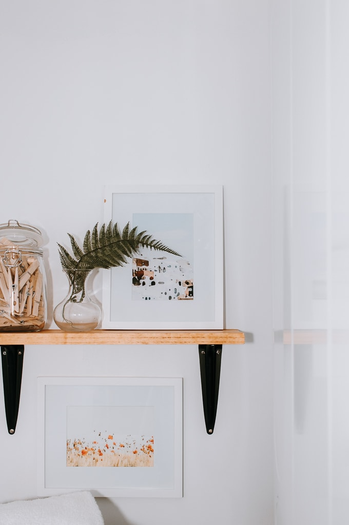 small shelf on a wall with artwork