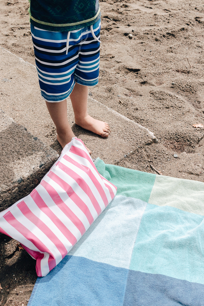 DIY swim bag on beach towel with sunscreen