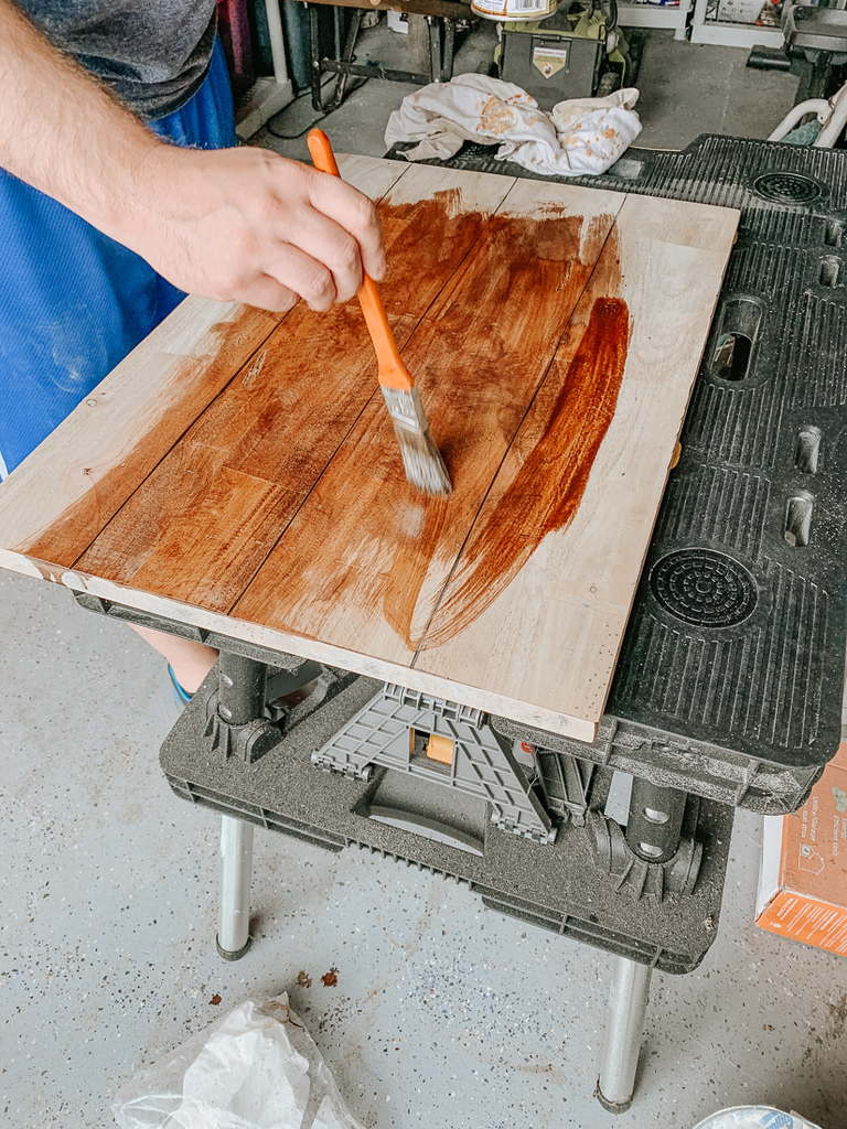 Apply stain with a paintbrush in the direction of the grain.