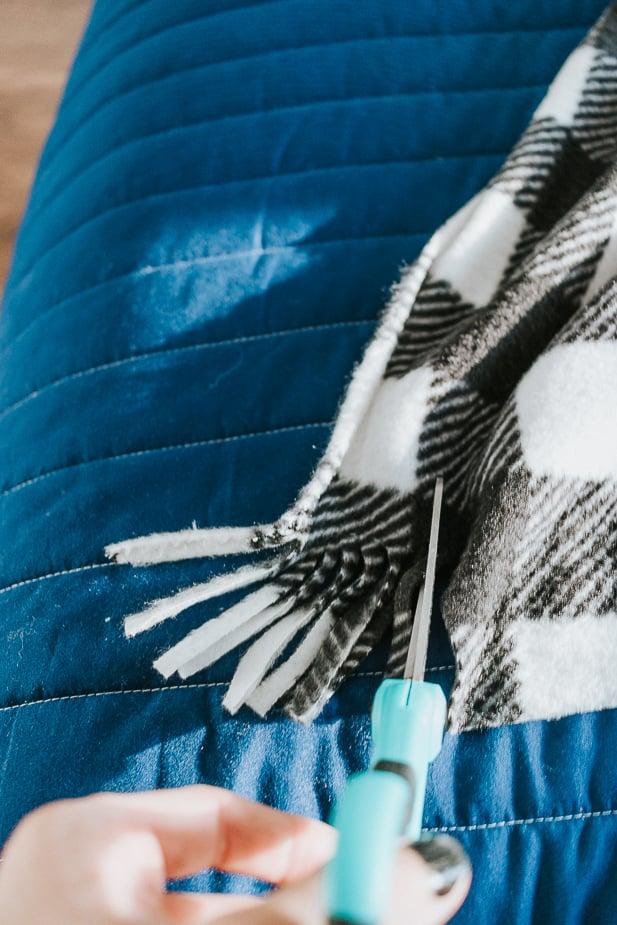 Scissors cutting fringe on a fleece blanket