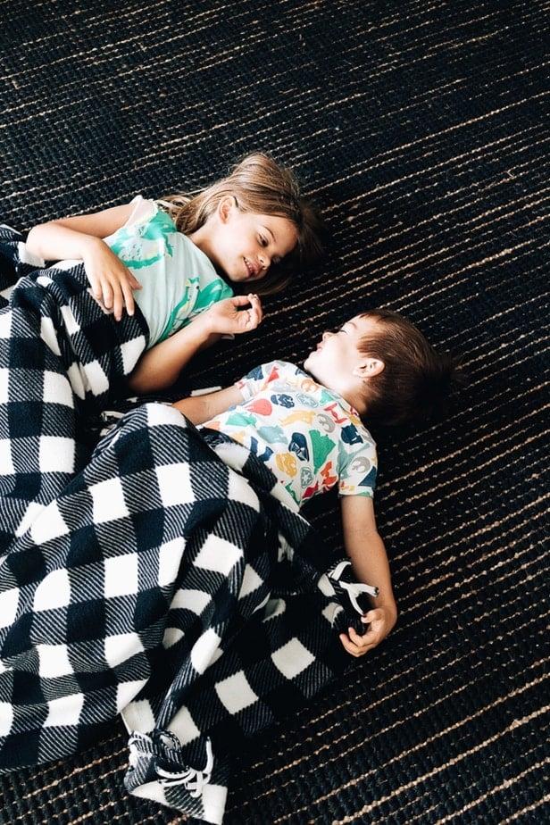 Two children snuggled under a fleece blanket