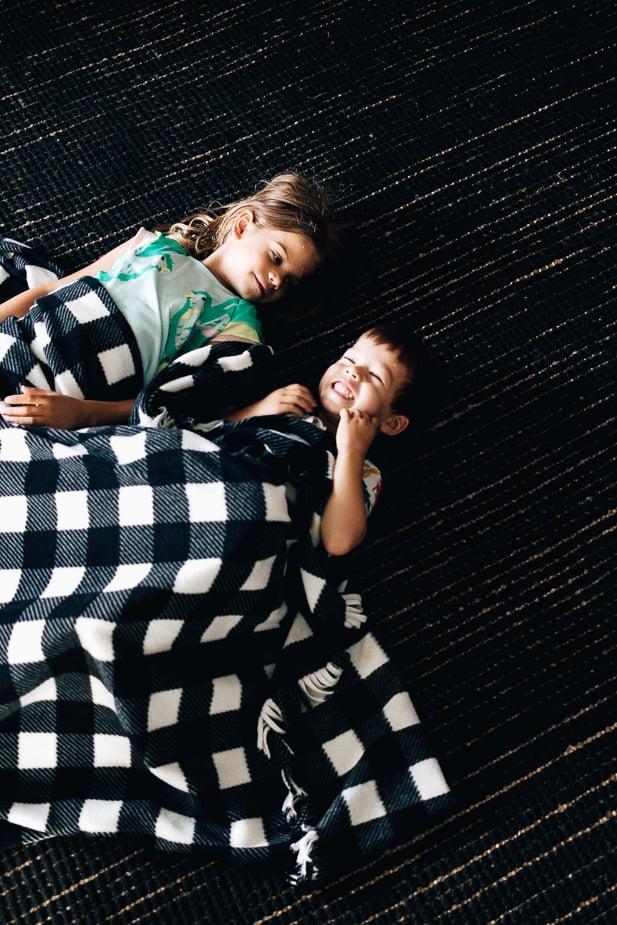 Children laying under a fleece blanket.