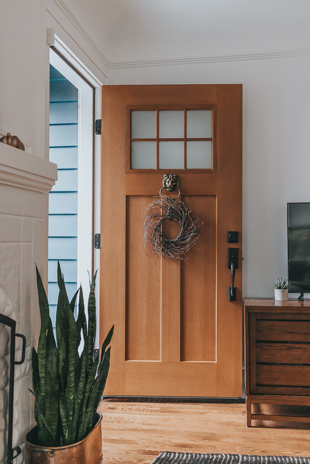 a door with a wreath on it below the doorknocker - how to hang a wreath on your front door