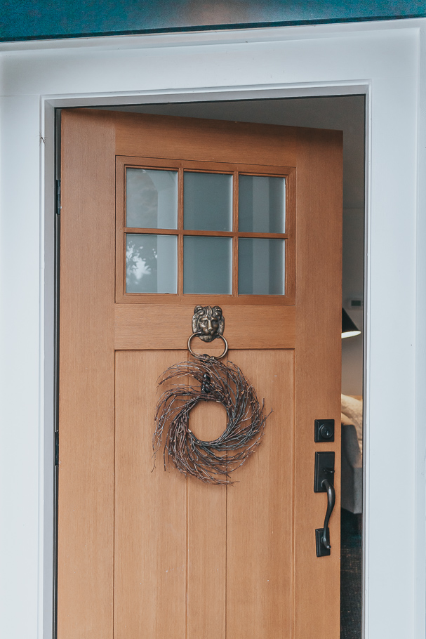 front door with grapevine wreath - how to hang a wreath without damaging your door.