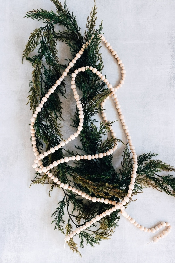 wood bead garland displayed on top of greenery garland