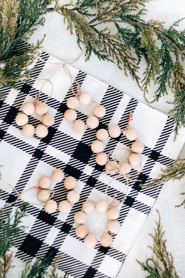 view of several wood bead ornaments on top of plaid fabric