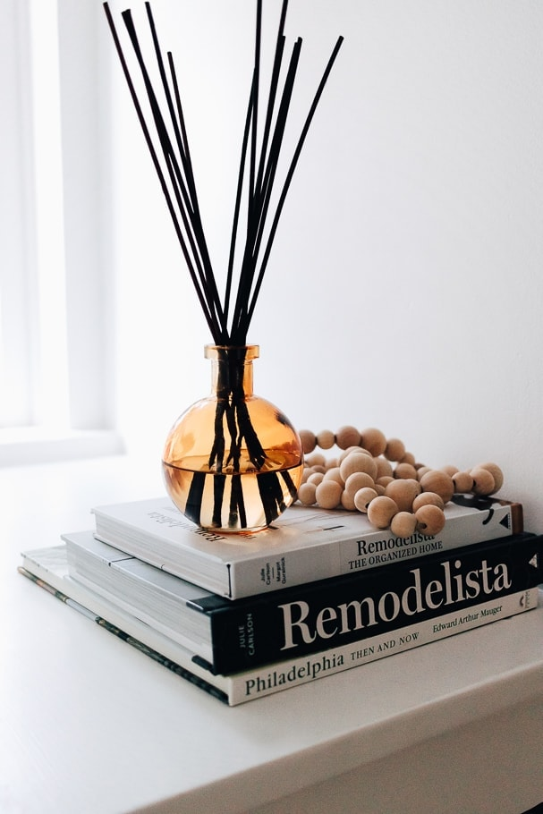 DIY essential oil reed diffuser on a stack of books with beads - home decor - decor hint