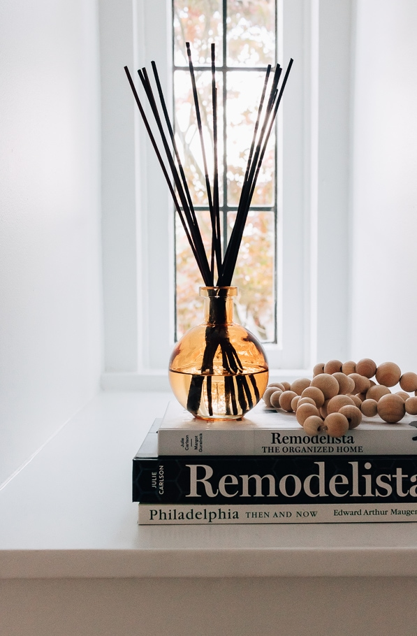 DIY reed diffuser with dark rattan diffuser sticks on stack of books in front of window