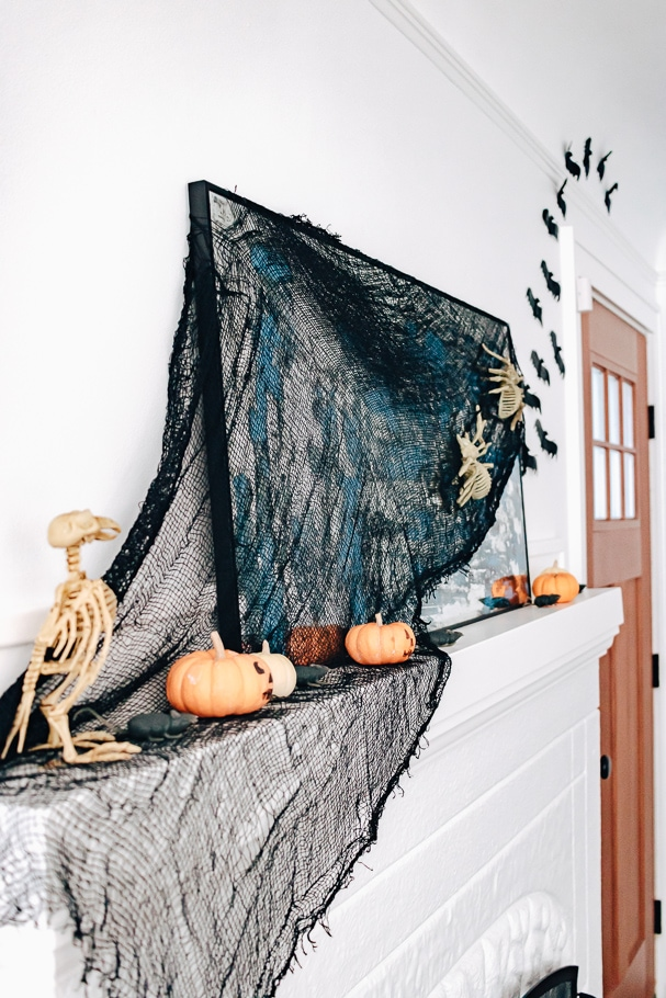 skeletons and pumpkins and bats on a mantel