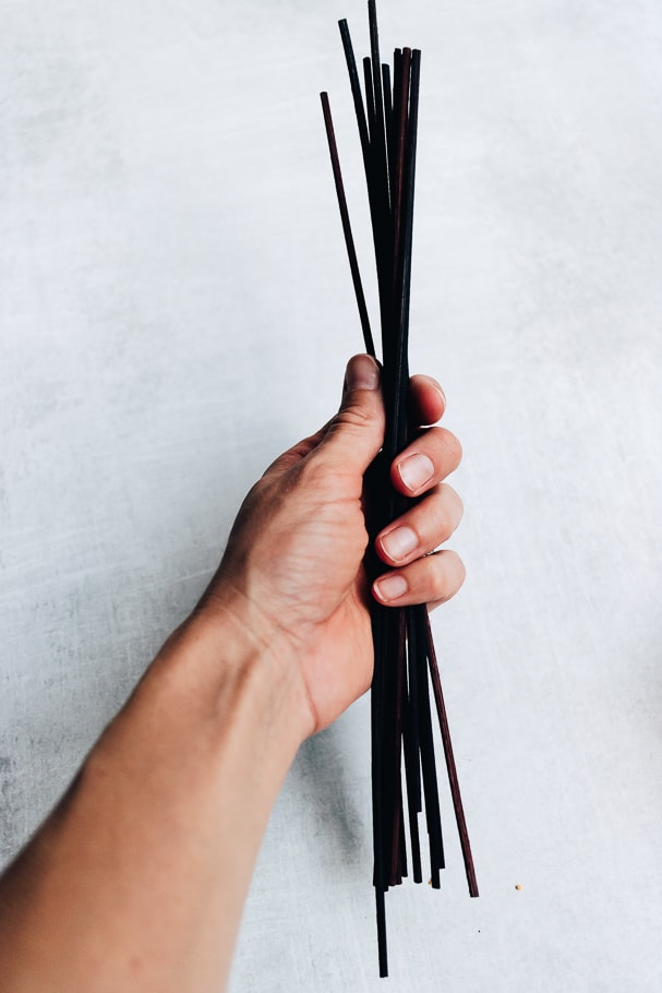 holding a bunch of dark rattan reed sticks