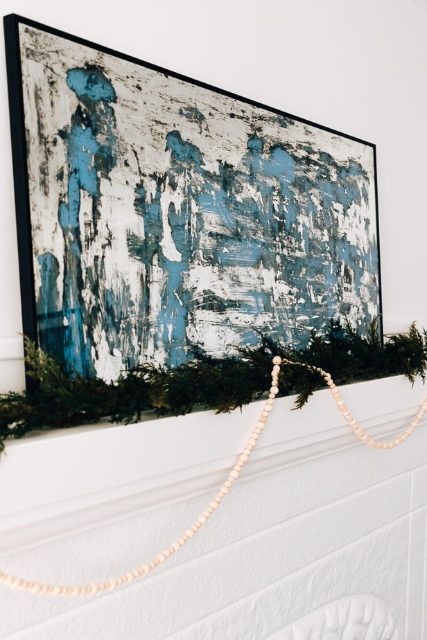 wood bead garland hanging from a mantel with greenery