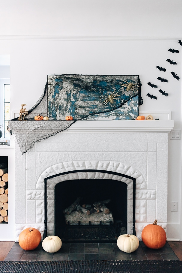 Halloween Mantel Ideas - fireplace dressed up for Halloween with bats, pumpkins and skeletons