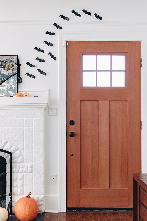 faux bats hung on wall by front door