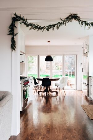 photo of a kitchen with christmas garland hanging on the entryway wall