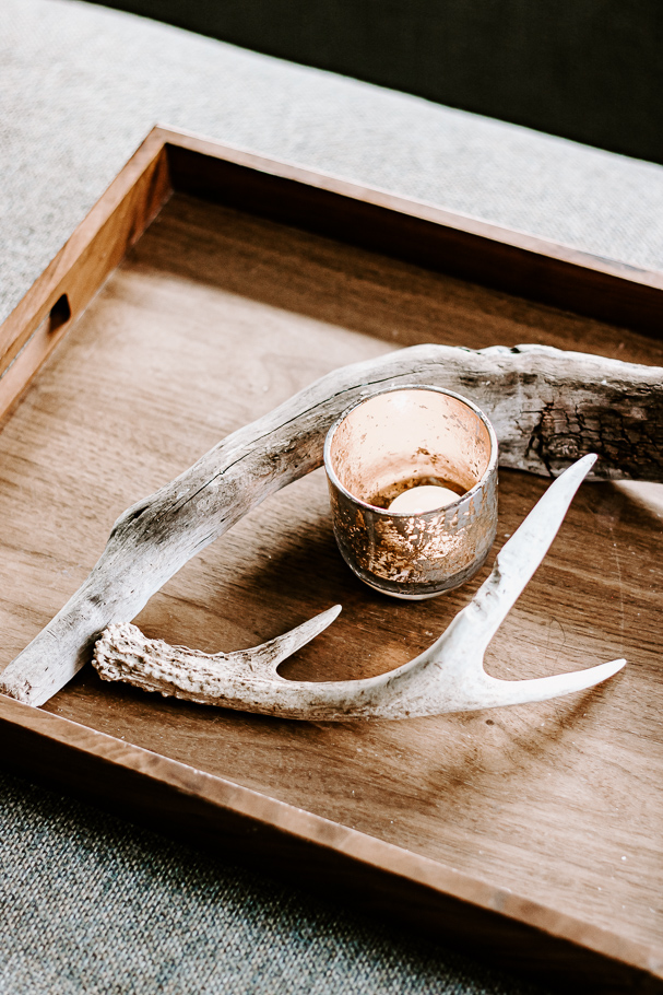 mercury glass candle with driftwood and antler decor on a tray