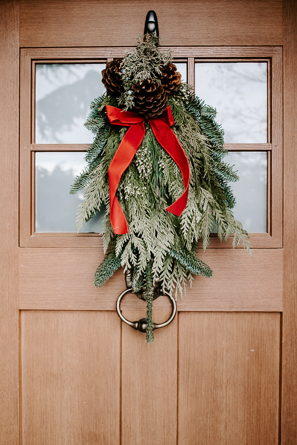 christmas swag with red ribbon on front door