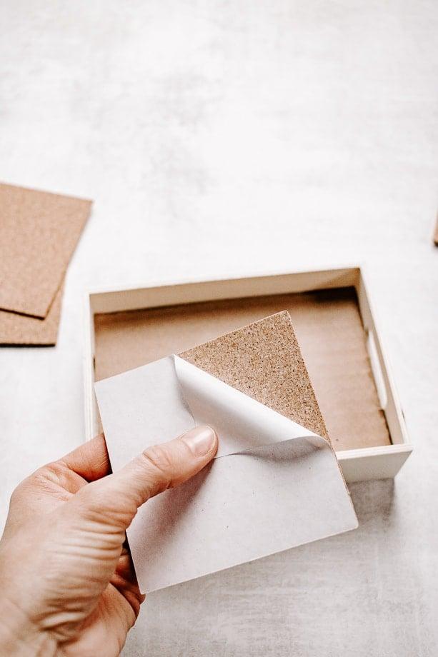 Peel adhesive off back of cork
