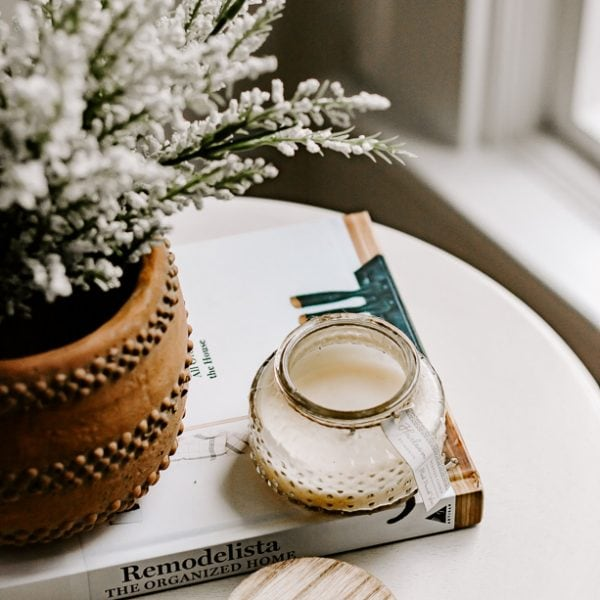 flowers on table in terra cotta pot with book and candle