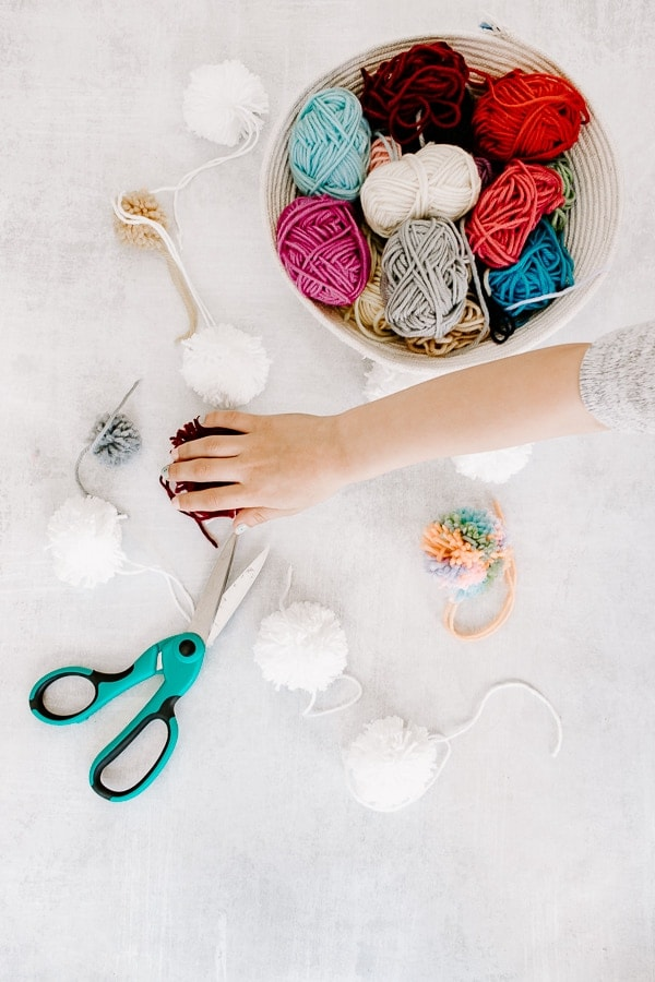 Basket of Yarn with Scissors and Fluffy Pom Poms