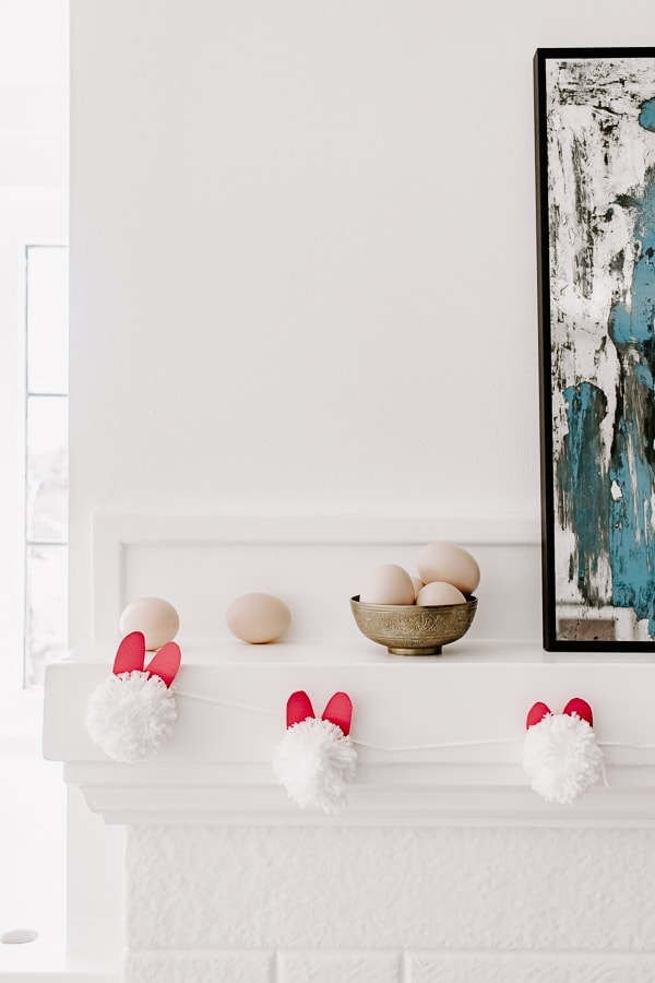 easter bunny garland hanging from a mantel