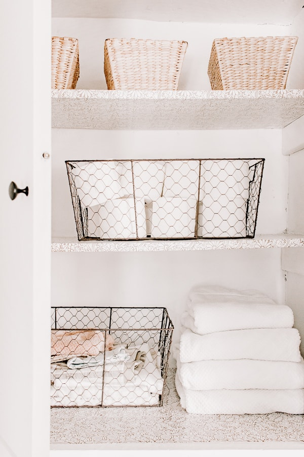 Small linen closet with wire baskets and folded towels