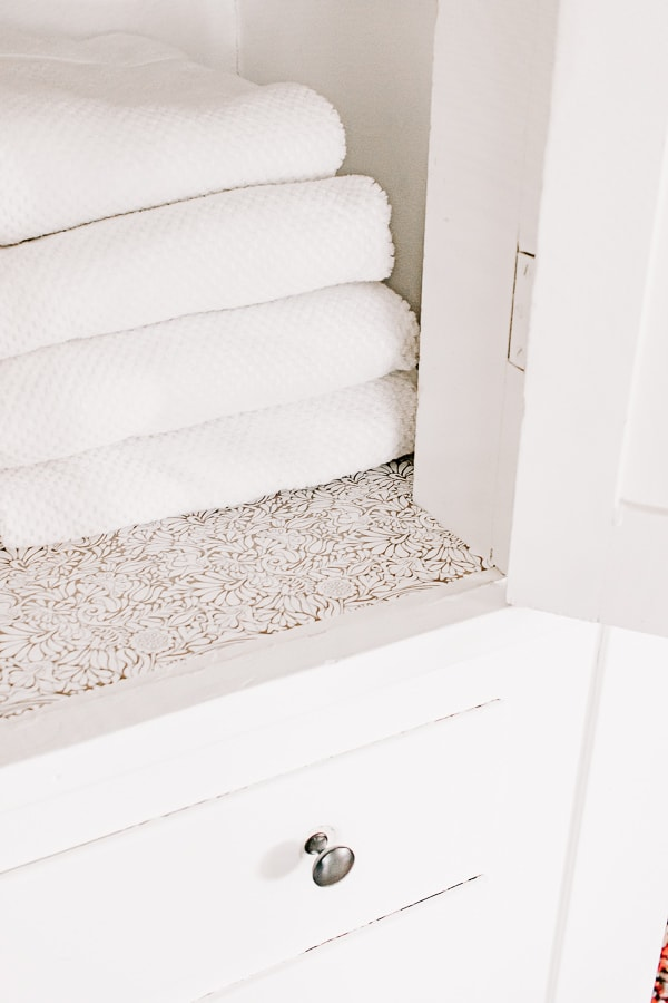 Inexpensive shelf liner adds a decorative touch to your linen closet