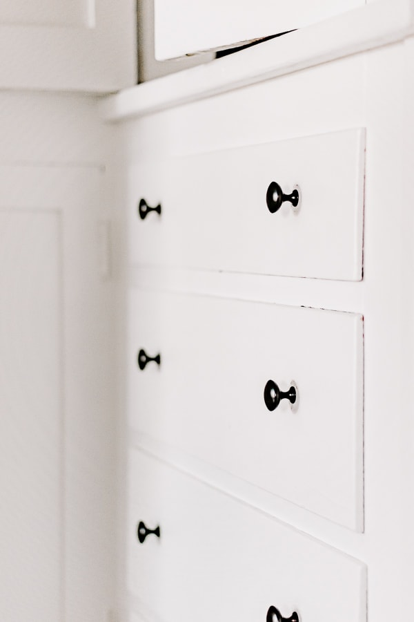 Black matte knobs can elevate the look of a plain white linen closet
