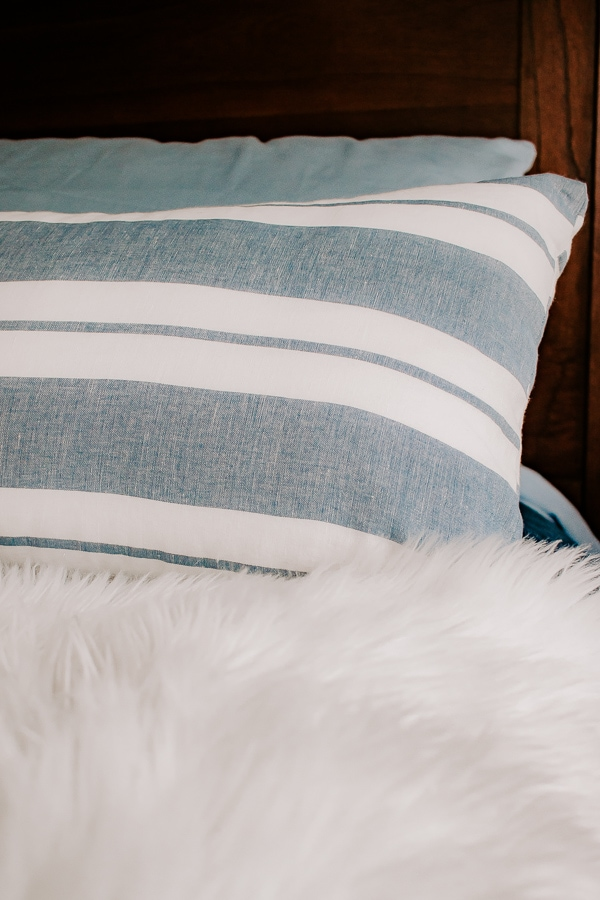 faux sheepskin rug on a bed with blue pillows