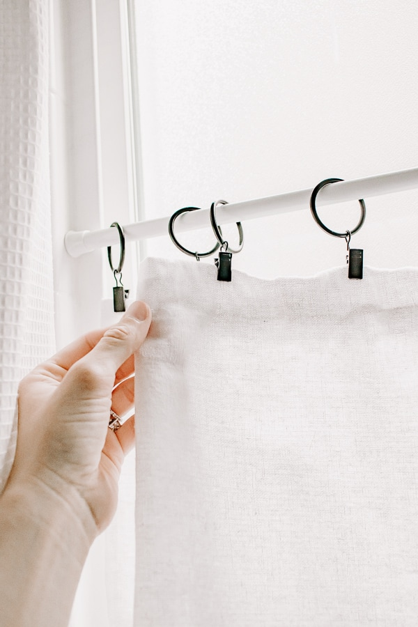 black clip rings with a white linen cafe curtain