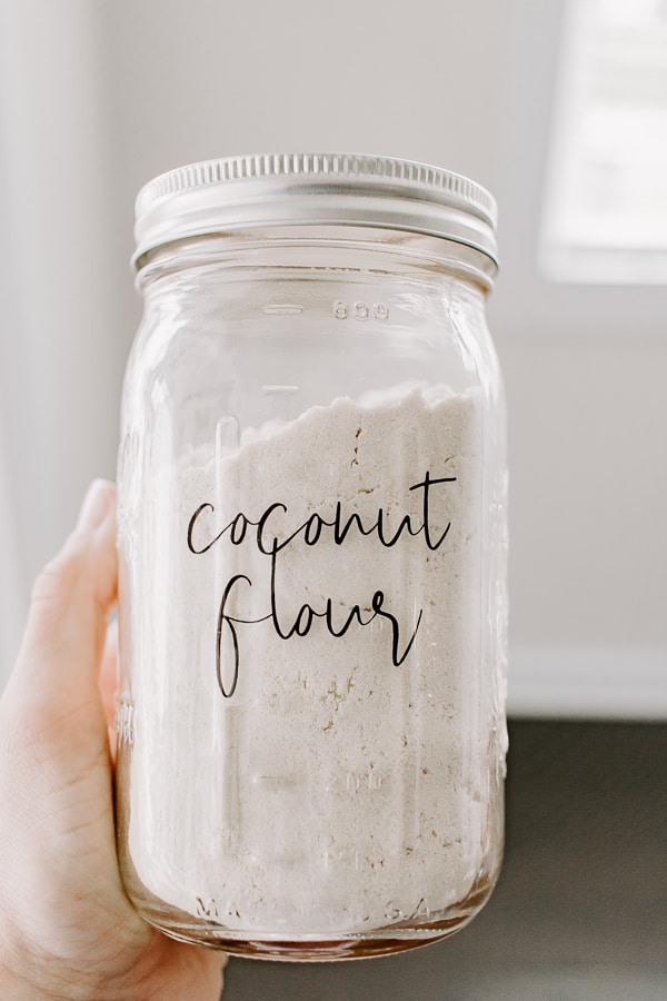 holding a mason jar labeled coconut flour
