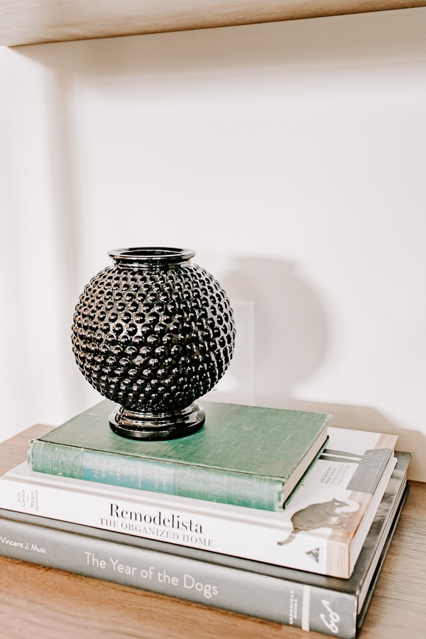 close up view of a small black vase on a stack of books