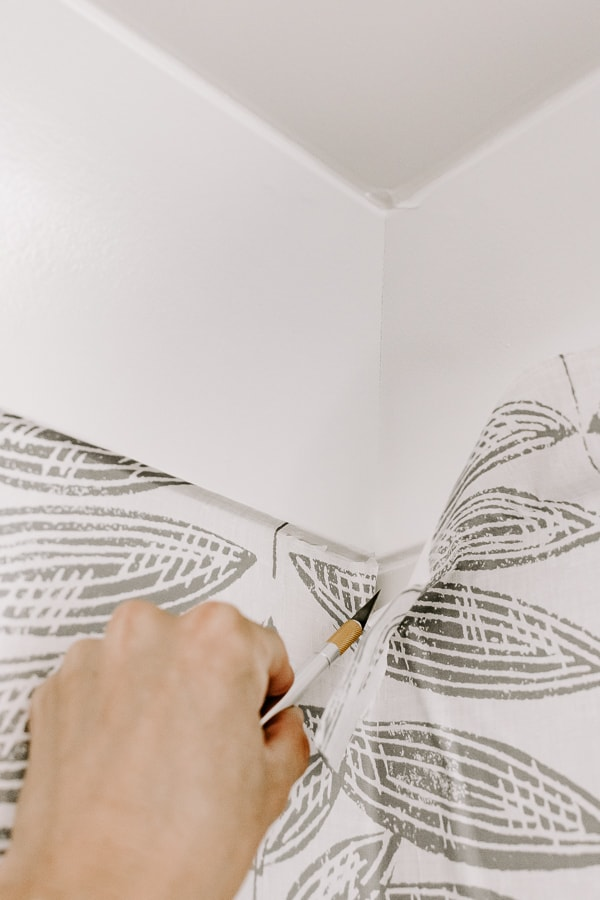 applying peel and stick wallpaper in a corner