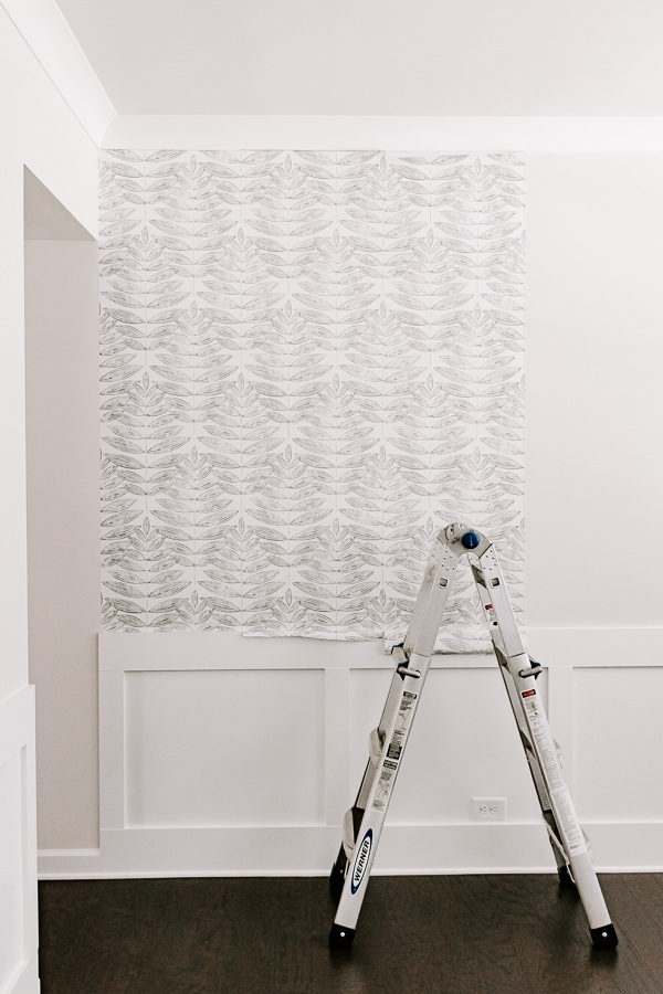 showing a ladder with a application of wallpaper - black and white gray leaf pattern