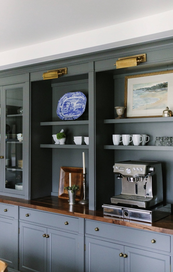 a navy open shelving with a barista coffee maker on it