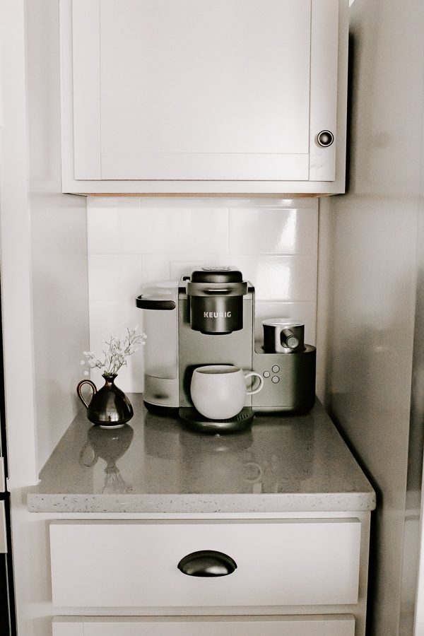 a simple coffee station with a keurig coffee maker and a small vase of baby's breath