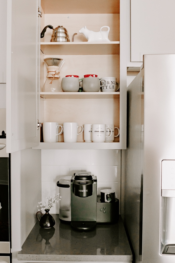 coffee maker on a counter with a cabinet open above showing coffee accessories and mugs