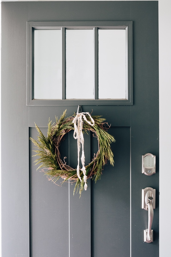 green wreath on a gray front door with a linen ribbon