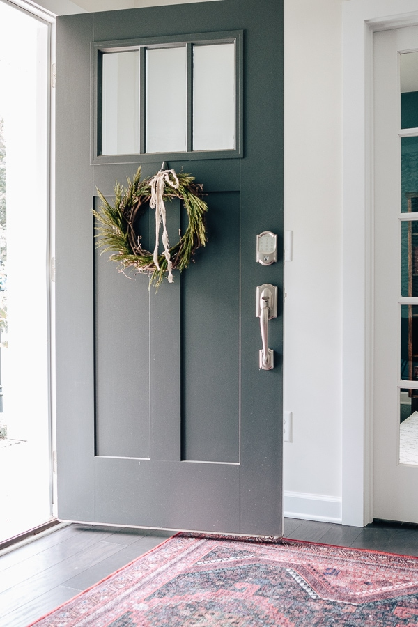 diy green wreath on a gray front door with a red rug in the foyer